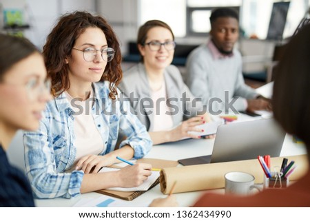 Group of contemporary people working in meeting focus on curly haired young woman in foreground, copy space #1362434990