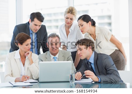 Group of content business colleagues with laptop at office desk