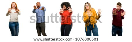Group of cool people, woman and man disgusted and angry, keeping hands in stop gesture, as a defense, shouting #1076880581