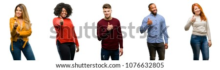 Group of cool people, woman and man smiling broadly showing thumbs up gesture to camera, expression of like and approval