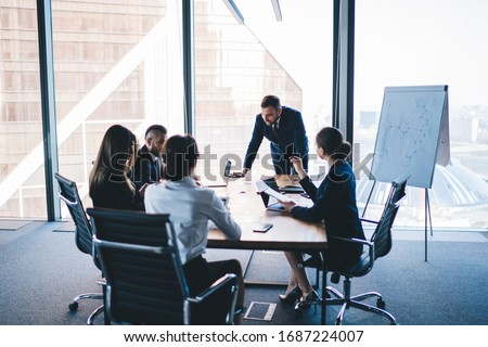 Group of coworkers in formal wear sitting at table in conference room and arguing about project of company development during meeting