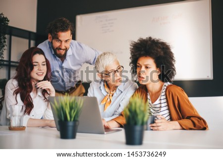 Group of coworkers sitting and working together on new startup project #1453736249