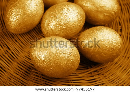 Group of crackle golden Easter eggs in wicker basket.