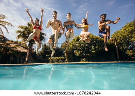 Group of crazy young people jumping into a swimming pool. Friends having fun at a holiday resort. #1078242044