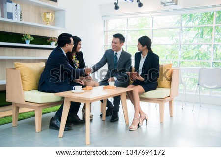 Group of creative business people having a meeting in a modern office cafe. Business people having conversation over new project