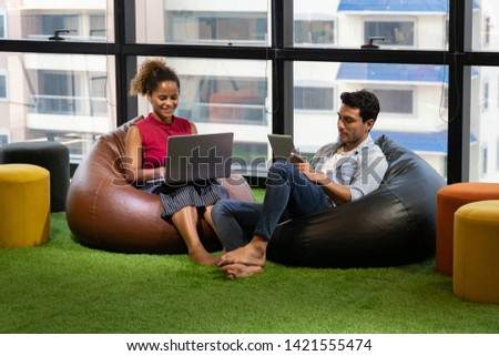group of creative designers brainstorming together in coworking space . comfortable position . Business man and young African American woman sittig on sofa presenting in  Modern office . drink coffee stock photo