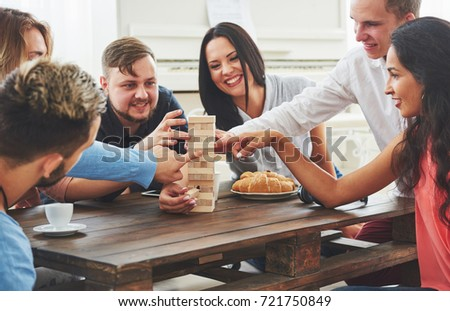 Group of creative friends sitting at wooden table. People having fun while playing board game. #721750849