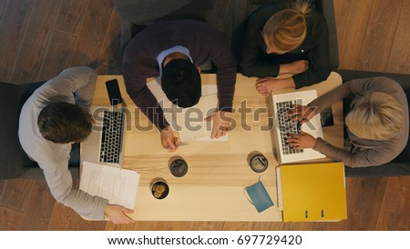 Group of creative people discussing, preparing important contract #697729420
