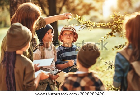 Group of curious school children with notebooks listening to their young female teacher while learning about nature together, looking at green leaf during ecology lesson in autumn forest on sunny day