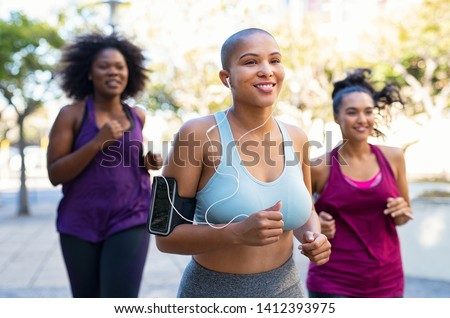 Group of curvy women jogging on track in park. Girls friends running together outdoor. Portrait of young bald woman jogging with oversize friends while listening to music on mobile phone.