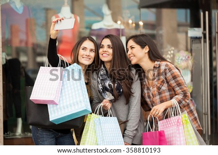 Group of cute female friends doing some shopping at a mall and taking a selfie with a smartphone