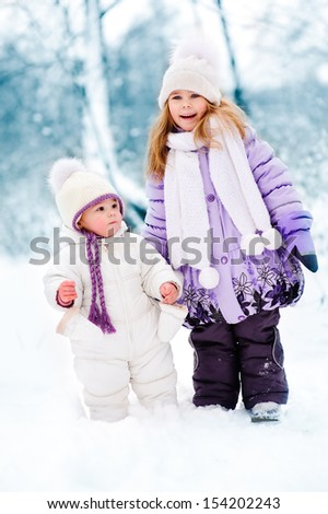 group of cute happy children walking in winter snow park. Two little girl in warm fashion clothes.