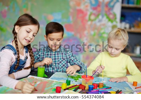 Group of cute kids painting with gouache