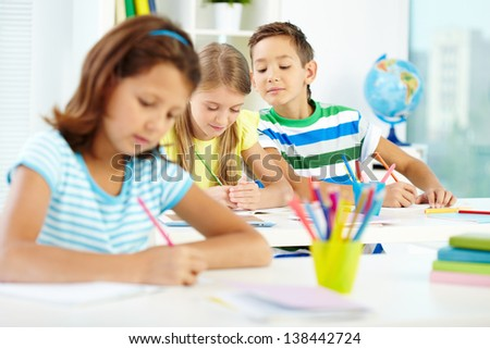 Group of cute schoolkids drawing at lesson