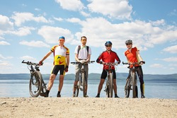 group of cyclists on the shore of a mountain lake. team outdoors. mountain bike