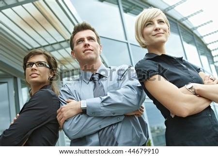 Group of dedicated young business people posing outdoor in front of office building.