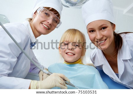Group of dentist, assistant and little girl looking at camera