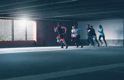 Group of determined young athletes urban running sprinting through a covered commercial car park in a training workout, sun flare side light and copy space