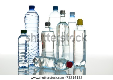 group of different mineral water bottles on reflective surface