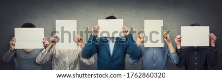 Group of different people, business team, each covering his face using a blank white paper. Teamwork thinking and cooperation process. Persons hiding identity behind an empty sheet, anonymous concept. Сток-фото ©