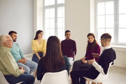 Group of different people sit in a circle and each talks about their problems during a therapy session at the rehabilitation center. Concept of help with alcohol and drug addiction.