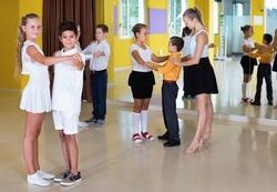 Group of diligent friendly  children dancing tango in dance studio