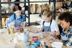 Group of diligent schoolkids sitting by table while making and painting self-made earthenware