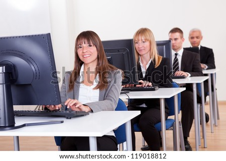 Group of diverse business people working in a support centre sitting at desks in front of computer monitors responding to email enquires