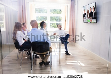 Group Of Diverse Businesspeople Looking At Television While Video Conferencing In Boardroom #1153862728