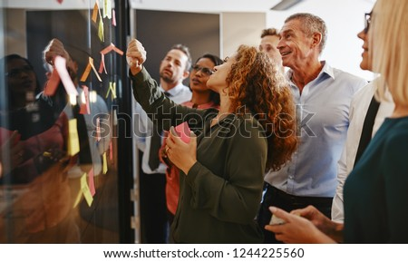 Group of diverse businesspeople strategizing with sticky notes on a glass wall while working together in a modern office Stock fotó ©