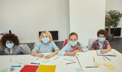 Group of diverse elementary school kids wearing protective mask during coronavirus pandemic looking cheerful while sitting together at the table in a classroom