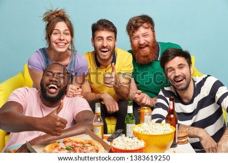 Group of diverse friends cheer as favourite team wins, show thumb up gesture, eat tasty pizza and popcorn, smile broadly, drink beer, isolated over blue background. People, entertainment, fun concept #1383619250