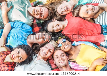 Group of diverse friends having fun outdoor - Happy young people lying on grass after picnic and laughing together - Friendship, unity, millennial and youth lifestyle concept #1316200214