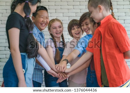 group of diverse kids hands of together joining for teamwork, community, togetherness and collaboration concept