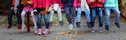 Group of diverse kids sitting together on the bench in the kindergarten, autumn outdoor, fashion and style