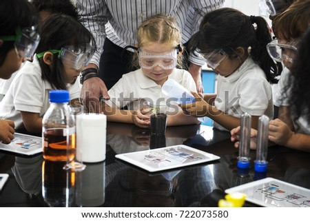 Group of diverse kindergarten students learning planting experiment in science laboratory class