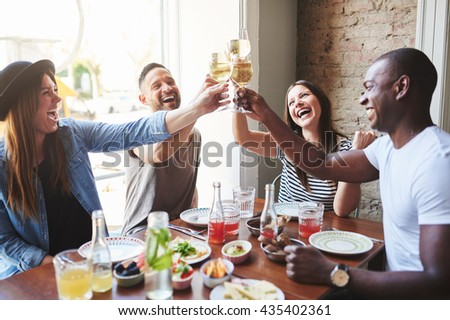 Group of diverse male and female laughing young adults putting their drinking glasses together at table in restaurant with large window