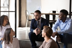 Group of diverse mates during break sit on stairs in office chatting enjoy informal friendly conversation, team listen to workgroup leader discussing current issues resting before meeting or training