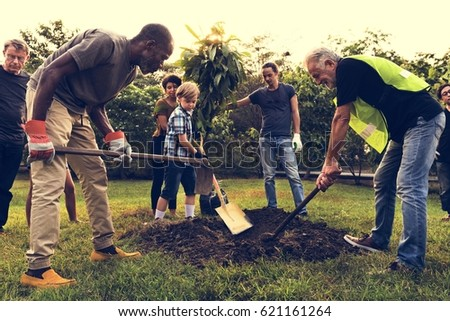 Group of Diverse People Digging Hole Planting Tree Together #621161264