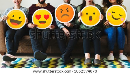 Group of diverse people holding emoticon icons