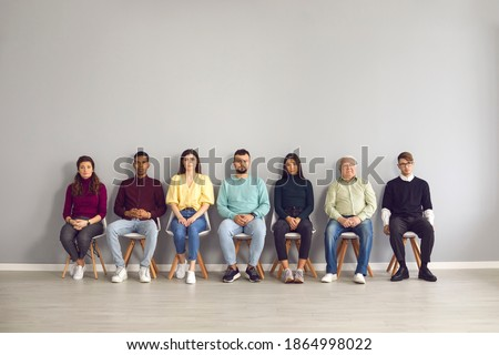 Group of diverse people in casual clothes waiting in line to see doctor. Male and female candidates of different ages and ethnicities sitting on chairs in row in office corridor before job interview