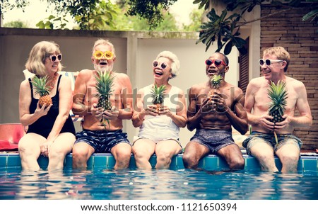 94241acd543be Group of diverse senior adults sitting at poolside holding pineapples  together #1121650394