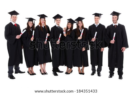 Group of diverse student graduates with their diplomas in their hands wearing gowns and mortar boards standing in a line isolated on white