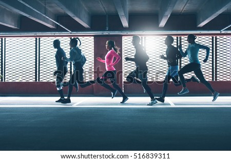 Group of diverse urban runners sprinting across the frame in an indoor car park as they workout backlit by the sun through a grid #516839311