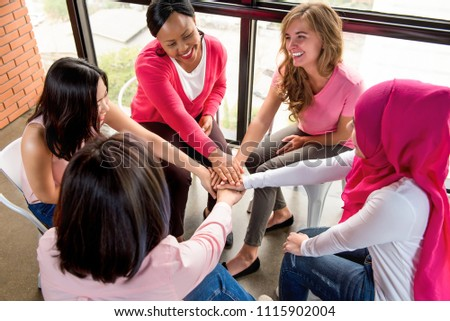 Group of diverse women put their hands together in stack empowering each other in breast cancer awareness campaign meeting