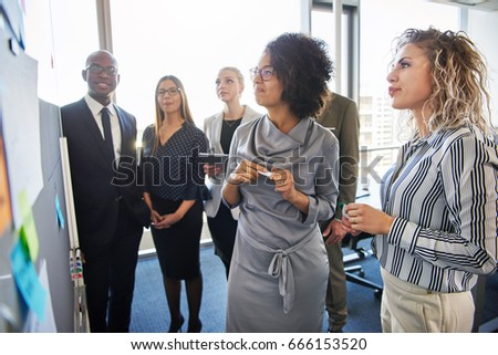 Group of diverse work colleagues having a planning and strategy session together on a whiteboard in a bright modern office