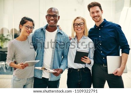 Group of diverse young businesspeople smiling confidently while standing arm in arm together in a bright modern office