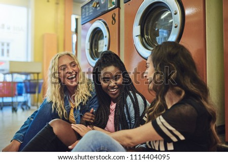 Group of diverse young female friends sitting on a laundromat floor talking and laughing together while doing laundry