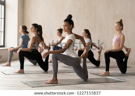 Group of diverse young sporty people doing Horse rider exercise, anjaneyasana pose, working out indoor, mixed race female students training, yoga lesson at club or studio. Well being, wellness concept