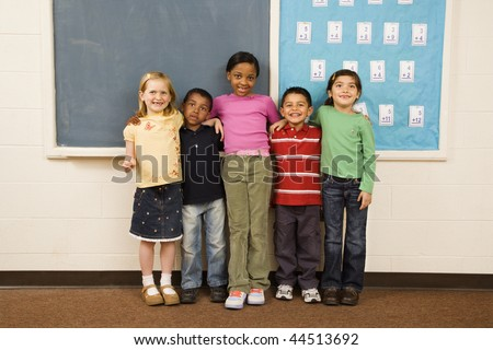 Group of diverse young students standing together in classroom. Horizontally framed shot.
